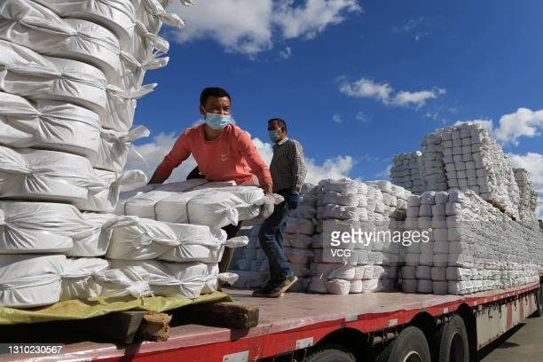 Workers load spools of yarn onto a truck at Xinjiang Xieyi Textile Technology Co., Ltd on March 30, 2021 in Kuqa, Xinjiang Uygur Autonomous Region of...