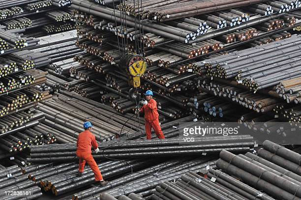 Workers load steel bars at Dongbei Special Steel Group on May 2 2013 in Dalian Liaoning Province of China