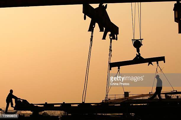 Workers load steel products on a crane at a factory of Shanghai Baosteel Group on January 9 2007 in Shanghai China Baosteel is one of the world's...