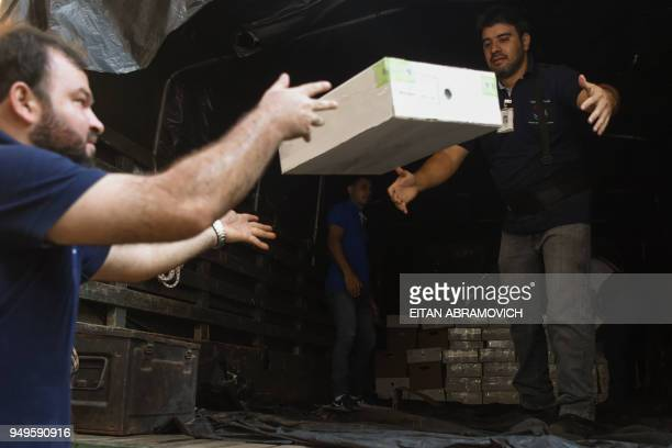 Workers load voting material into a truck ahead of the upcoming April 22 presidential elections in Asuncion on April 21 2018 Opinion polls give the...
