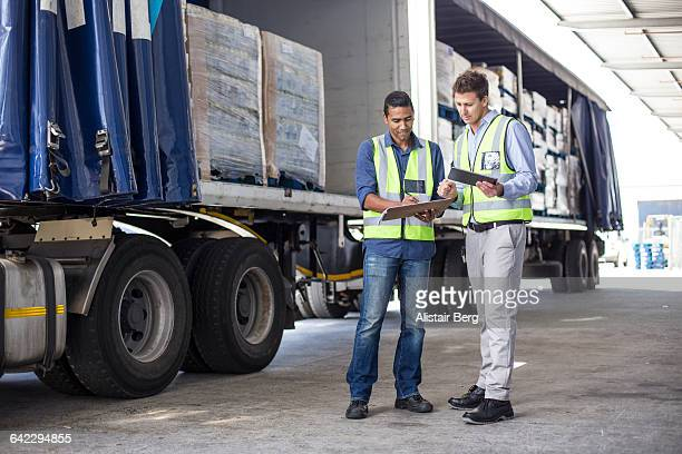 Workers loading a lorry at a large warehouse