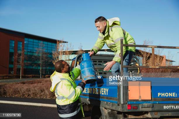 workers loading a truck with gas canisters - cylinder stock pictures, royalty-free photos & images