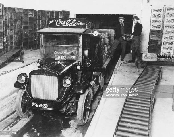 Workers loading crates of CocaCola bottles onto a truck at the plant circa 1930