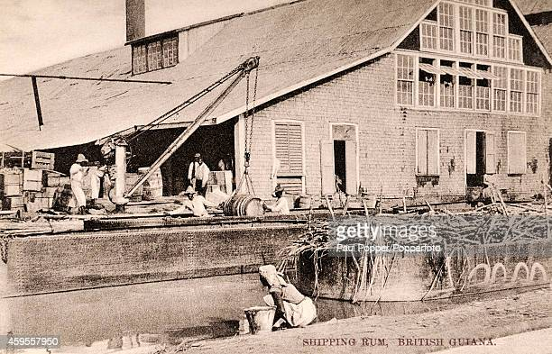 Native workers loading rum for export from British Guiana circa 1910