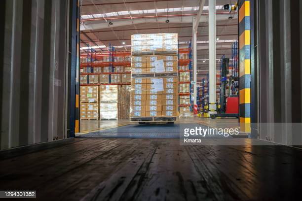 workers loading truck with forklift. - luggage hold stock pictures, royalty-free photos & images