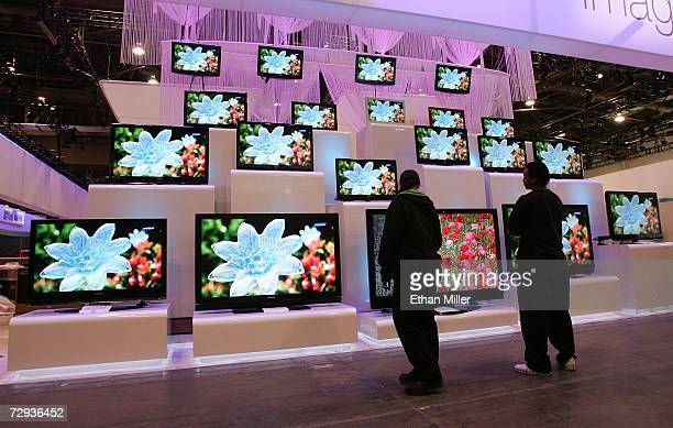 Workers look at a display of televisions by Samsung at the Las Vegas Convention Center as preparations continue for the opening of the 2007...