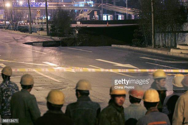 Workers look at a land cavein site near Jingguangqiao Bridge on the east Third Ring Road on January 3 2006 in Beijing China Sewage leaked from a...