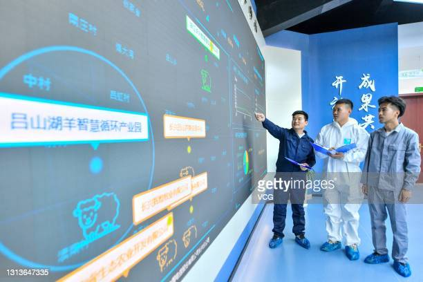 Workers look at a real-time display screen at an intelligent sheep farm on April 21, 2021 in Changxing County, Zhejiang Province of China.