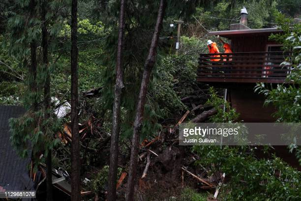 Workers look at debris from a home that was swept down a hill by a mudslide during a rain storm on February 14 2019 in Sausalito California 50 homes...