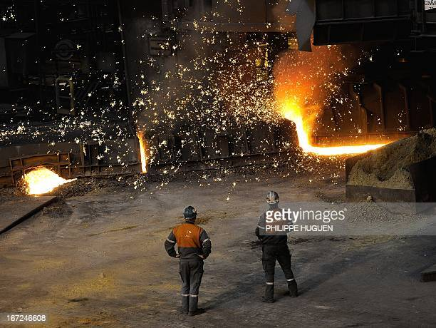 Workers look at hot steel at the ArcelorMittal steel plant of GrandeSynthe northern France on April 22 2013 AFP PHOTO PHILIPPE HUGUEN
