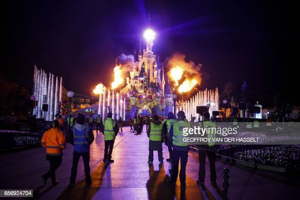 Workers look at the Sleeping Beauty Castle being illuminated during a night rehearsal on March 21 2017 ahead of celebrations marking the 25th...