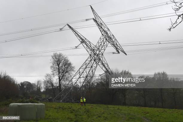 Workers look on as a damaged very high voltage electrical pylon lies in a field in Montabot western France on December 11 after an alleged act of...