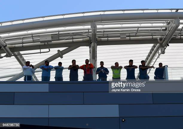 Workers look on as players of the Los Angeles FC practice for the first time on the field at the Banc of California Stadium on April 18 2018 in Los...