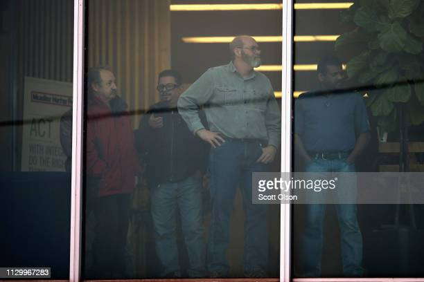 Workers look out an office window following a shooting at the Henry Pratt Company on February 15 2019 in Aurora Illinois Five people were reported...
