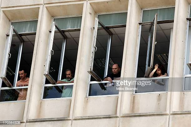 Workers look out from windows as they occupy the headquarters of the Greek public broadcaster ERT in Athens on June 12 2013 in Athens Greece...