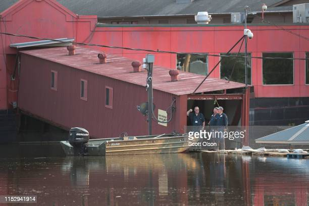 Workers look out over floodwater from the Mississippi River from the entrance of a riverboat casino on May 31 2019 in Alton Illinois The...