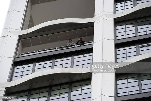 Workers look over a balcony after the New York City Medical Examiner's van drove out of a garage with the body of fashion designer L'Wren Scott the...