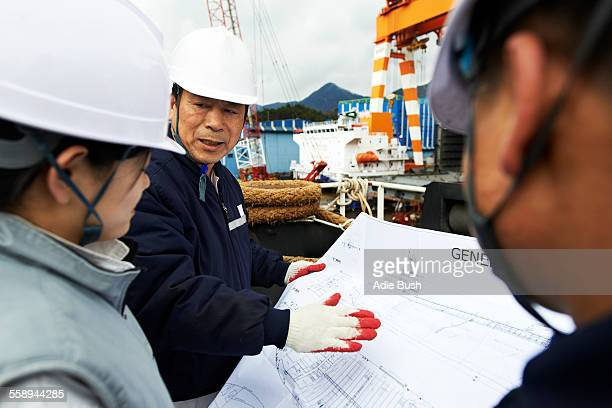 Workers looking at plans at shipyard, GoSeong-gun, South Korea
