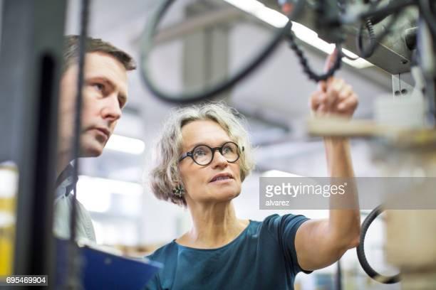 Arbeiter Druckmaschine zu betrachten und zu diskutieren