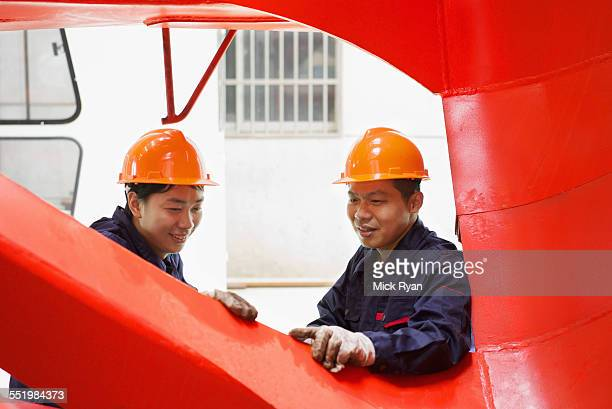 Workers looking at quality of work in crane manufacturing facility, China