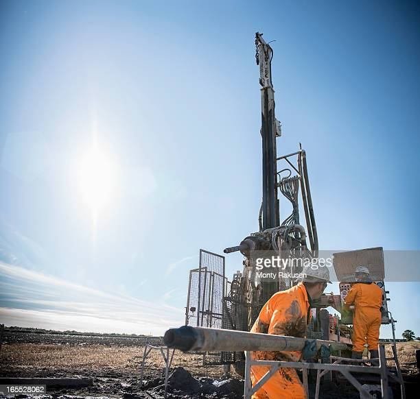 Workers looking for coal seams with drilling rig at surface coal mine