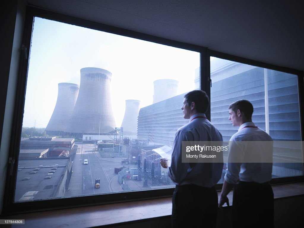 Workers looking out over power station : Stock-Foto
