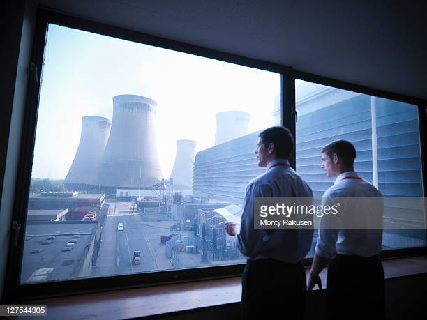 workers looking out over power station - nuclear power station stock pictures, royalty-free photos & images