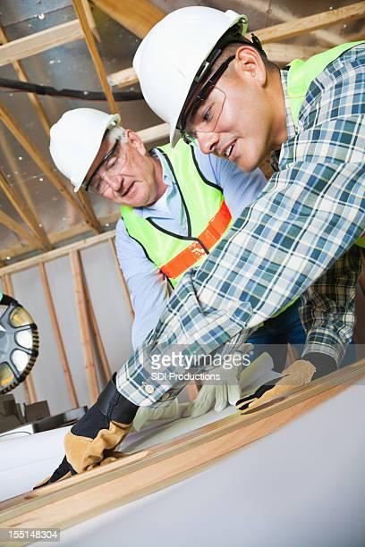 Arbeitnehmer über Gebäude Plänen in Baustelle