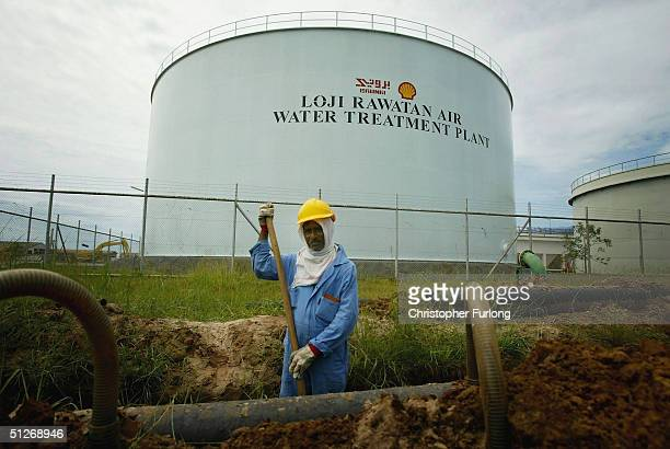 Workers maintain pipes at oil and gas processing facilities at Seria September 7 2004 in Brunei Brunei produces around 218000 barrels a day of crude...