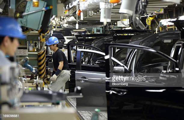 Workers make a final inspection on Mitsubishi Motors Corp vehicles on the production line of the Mitsubishi Motors Mizushima plant in Kurashiki...