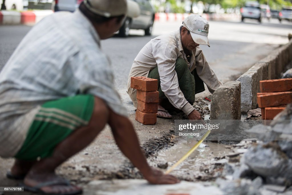 Workers make a measurement at a construction site on the side of a road in Yangon, Myanmar, on Monday, June 12, 2017. When the country opened to the outside world in 2011 after decades of military rule, the former British colony held promise as one of the worlds hottest tourist destinations, a last frontier for adventure travel. But it hasn't worked out that way. A construction glut has flooded Myanmar with unused hotel rooms, and poorly regulated building has damaged national treasures like the archaeological site of Bagan. Photographer: Taylor Weidman/Bloomberg via Getty Images