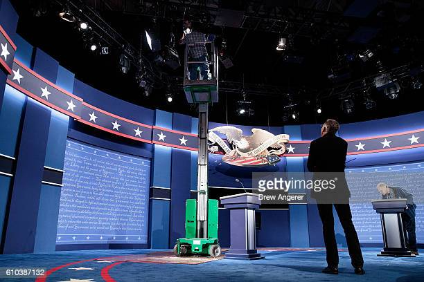 Workers make adjustments to the set for the first US presidential debate at Hofstra University on September 25 2016 in Hempstead New York Democratic...