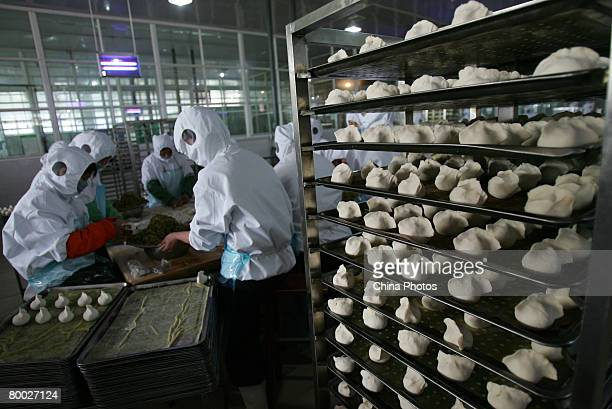 Workers make Chinese buns at a breakfast food factory on February 27 2008 in Xian of Shaanxi Province China China said it is making full efforts to...