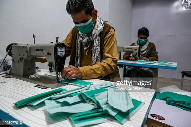 Workers make facemasks with sewing machines at a small factory during a government-imposed lockdown as a preventive measure against the COVID-19...