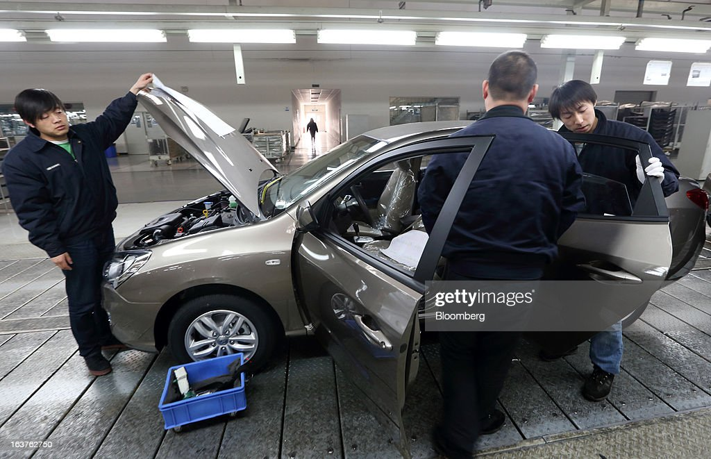 Workers make final inspections on a Beijing Hyundai Motor Co. car on the production line at the company's plant in Beijing, China, on Friday, March 15, 2013. The joint venture between Beijing Automotive Industry Holding Co. and Hyundai Motor Co., has three plants in the city, manufacturing 11 kind of models. Photographer: Tomohiro Ohsumi/Bloomberg via Getty Images