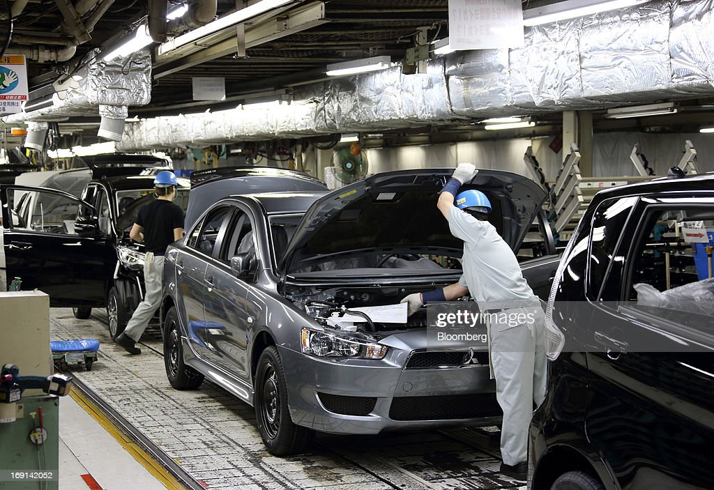 Workers make final inspections on Mitsubishi Motors Corp. vehicles on the production line of the Mitsubishi Motors Mizushima plant in Kurashiki City, Okayama Prefecture, Japan, on Monday, May 20, 2013. Nissan will start selling the first minicar it jointly developed with Mitsubishi Motors in Japan next month amid increasing demand from the nation's consumers for smaller and cheaper vehicles. Photographer: Tomohiro Ohsumi/Bloomberg via Getty Images