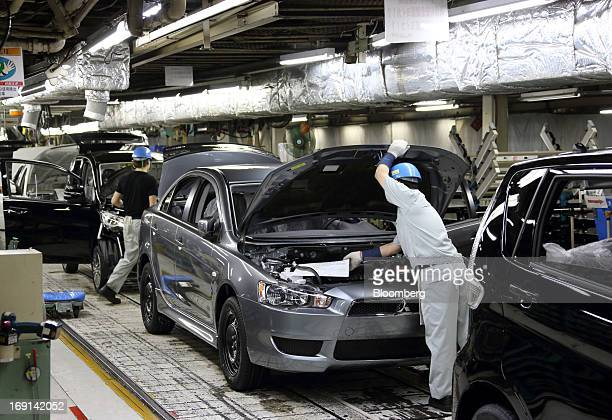 Workers make final inspections on Mitsubishi Motors Corp vehicles on the production line of the Mitsubishi Motors Mizushima plant in Kurashiki City...