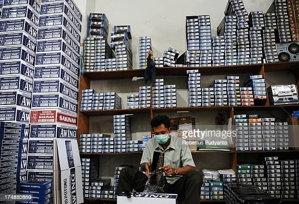 Workers make finishing touches to skull caps before they are put in a box at Awing traditional Muslim skull cap manufacturers on July 29, 2013 in...