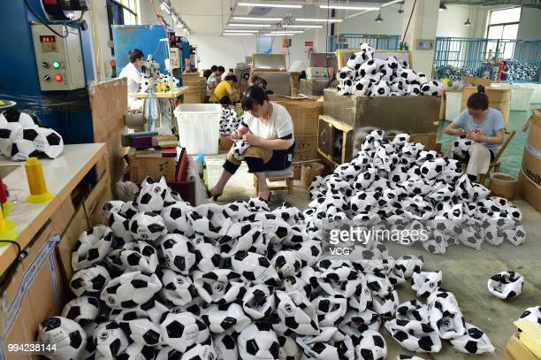 Workers make footballs overtime to process additional football orders from Russian Brazilian and other overseas customers at the producing department...