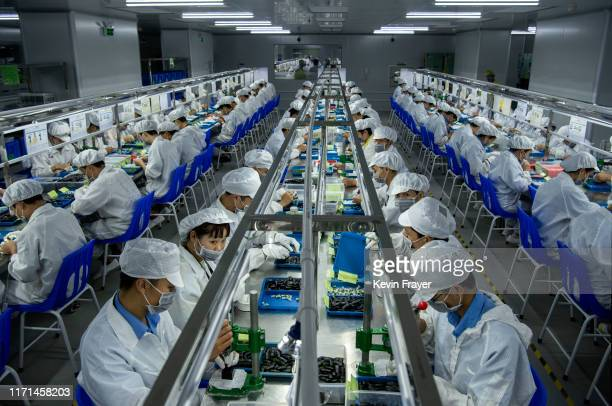 Workers make pods for e-cigarettes on the production line at Kanger Tech, one of China's leading manufacturers of vaping products, on September 24,...