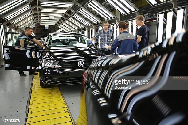 Workers make quality control checks on a VW Jetta automobile on the production line for Volkswagen AG and Skoda AS vehicles at the Gaz auto plant...