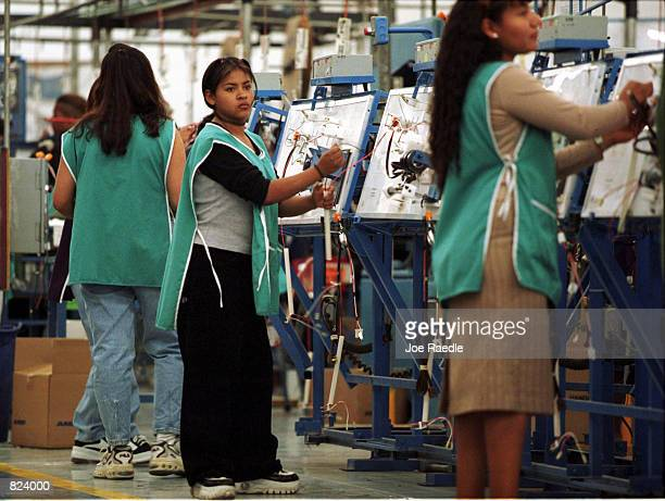 Workers make wire harnesses for cars in a maquila in Ciudad Juarez Mexico From Matamoros Mexico to Tijuana US owned maquiladoras employ a large work...