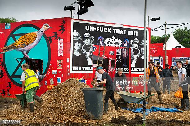 Workers making final preparations putting woodchip onto the muddy floor in the Shangri La field Glastonbury Festival 2016 The Glastonbury Festival is...