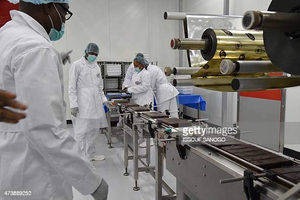 Workers man machinery following the innauguration of the French chocolate manufacturers CEMOI factory in Abidjan on May 18 2015 AFP PHOTO / ISSOUF...