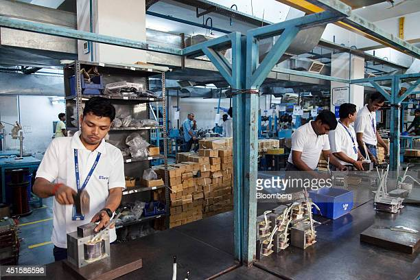 Workers manually fill the cores of transformers on the transformer line at the SuKam Power Systems Ltd power inverter factory in Gurgaon India on...