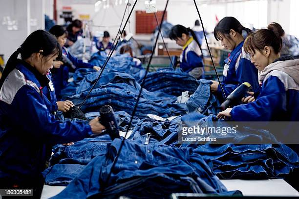 Workers manufacture blue jeans in Congshin textile factory on February 9 2012 in Xintang Guangdong province ChinaThe town of Xintang nicknamed the...