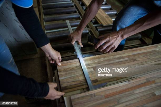 Workers measure the width of a wooden floorboard using a vernier caliper in a workshop at the Eiwlee Industrial Co factory in Pongyangkok Lampang...