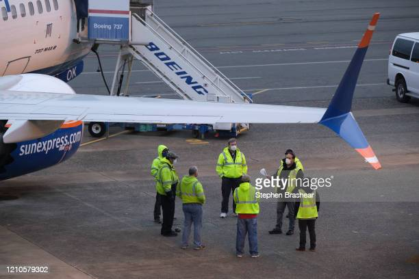 Workers meet on the flight line near Boeing 737 MAX factory on April 21 shortly after company resumed operations, in Renton, Washington. The company...