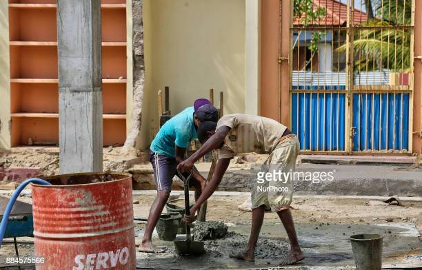 Workers mix cement during construction to rebuild the Mankumpan Pillayar Hindu temple in Jaffna Sri Lanka This temple was bombed and destroyed by the...