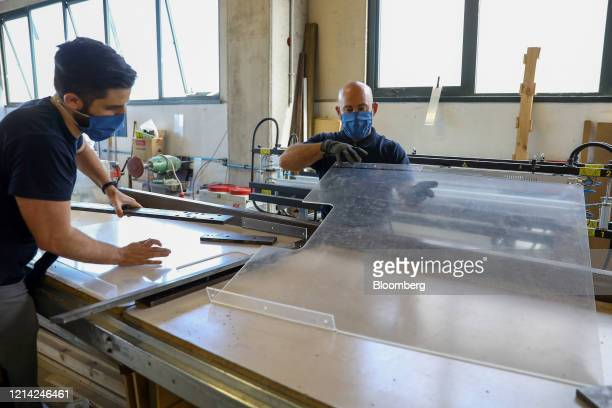 Workers model plexiglass screens after warming them at Plexismart Srl in Guidonia close to Rome Italy on Wednesday May 20 2020 Floortoceiling...